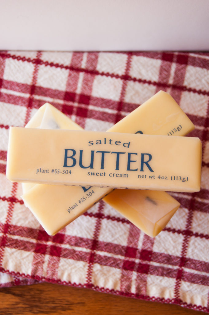 Stack of 4 sticks of butter on a red checked cloth