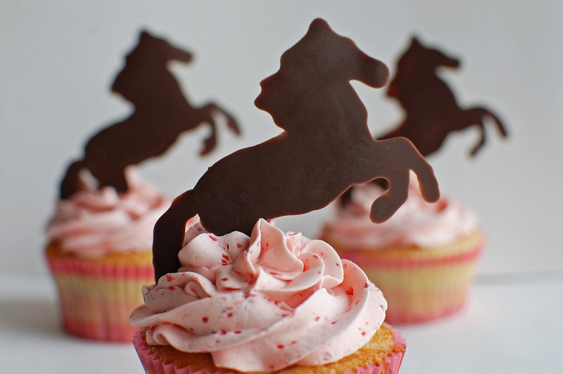 Hand piped chocolate horses on top of strawberry cupcakes swirled with strawberry buttercream