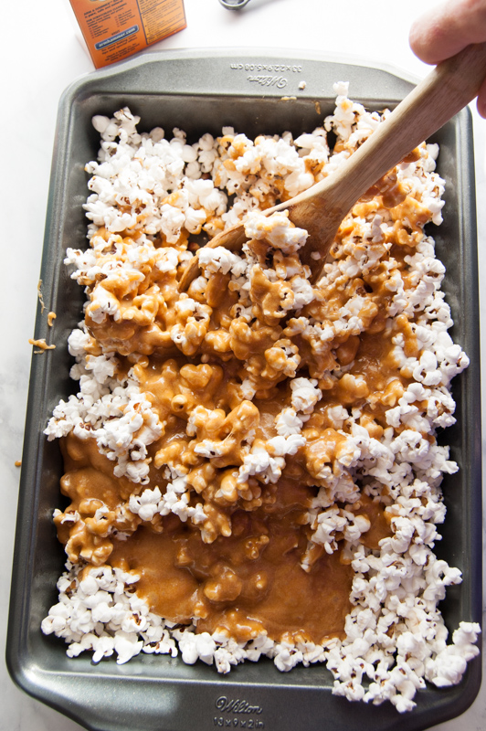 stirring caramel into popcorn