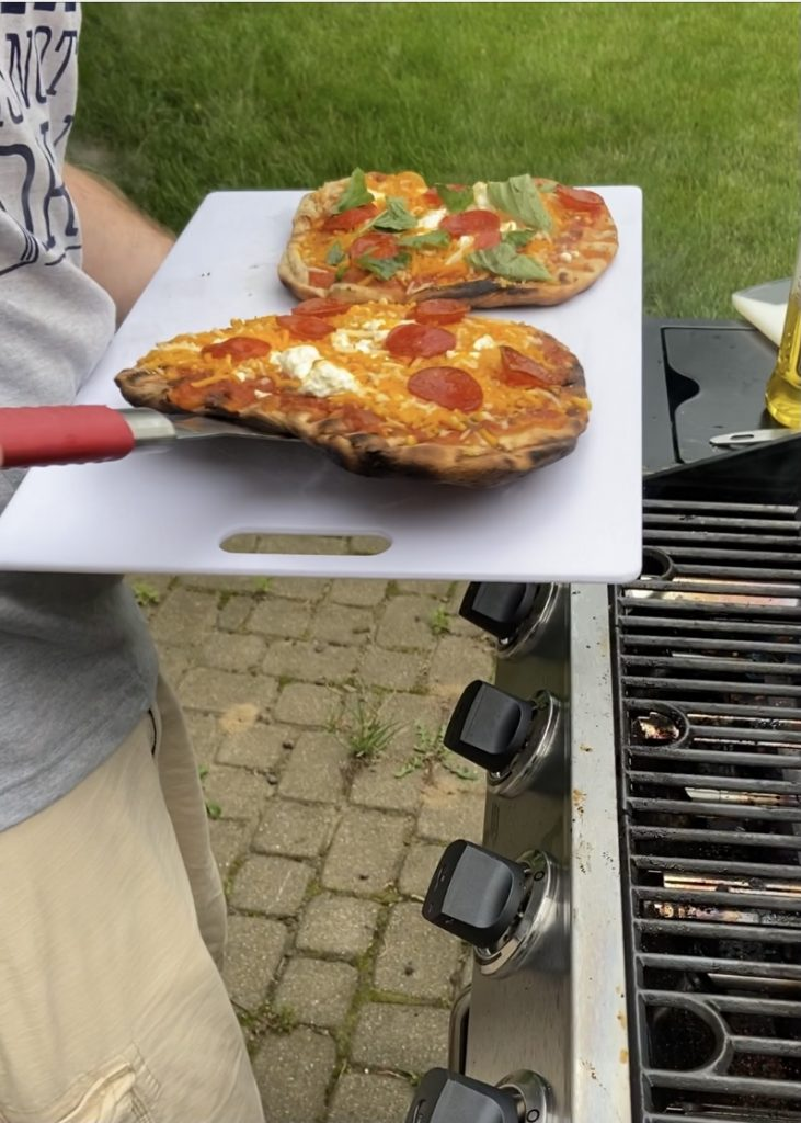taking the pizza off the grill